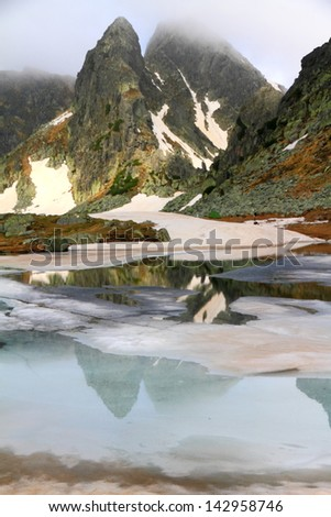 Glacier lake with ice and snow melting in foggy weather on the mountain