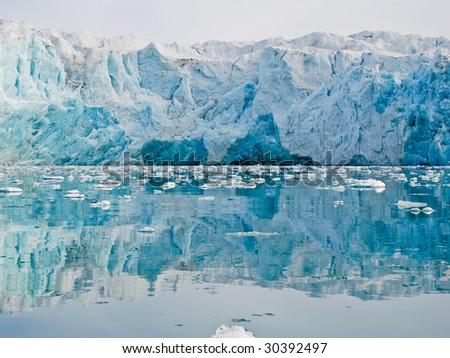 Glacier reflecting in the calm waters of fjord