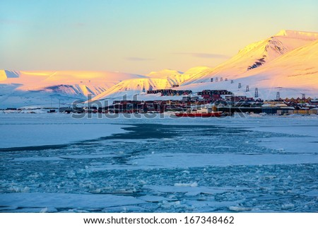 Glacier with small iceberg at the Arctic North Pole, Svalbard. In background is Longyearbyen city, sunset light  - stock photo
