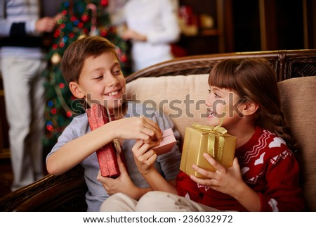 Glad boy and girl with Christmas presents in boxes - stock photo