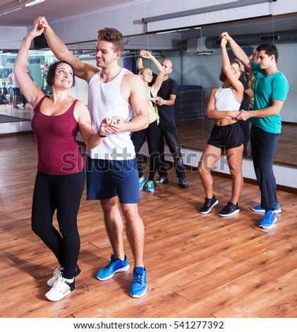 Glad dancing couples learning salsa at dance class