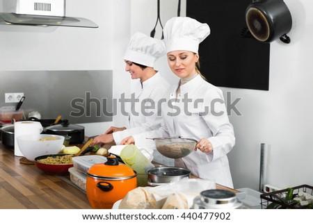 Glad diligent female chefs preparing food on restaurant kitchen - stock photo