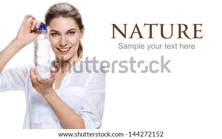 glad european woman & bottle of clear water / attractive girl of the European appearance in a white shirt holding a plastic bottle of clean clear water - isolated on white background  - stock photo