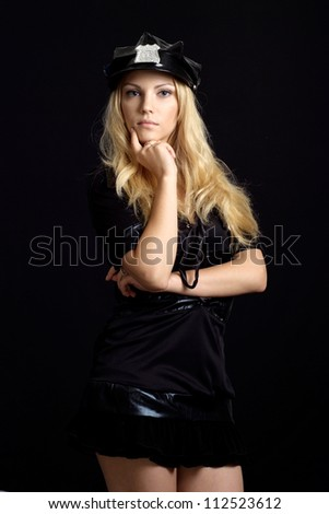 Glad girl in a uniform of  police officer on a black background - stock photo