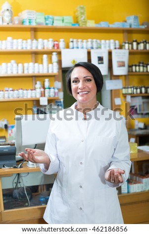 Glad mature female woman in uniform standing with dietary supplements in pharmacy