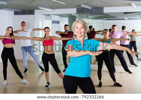 glad men women of different ages posing in fitness studio