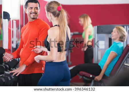 Glad smiling people  weightlifting training in modern health club