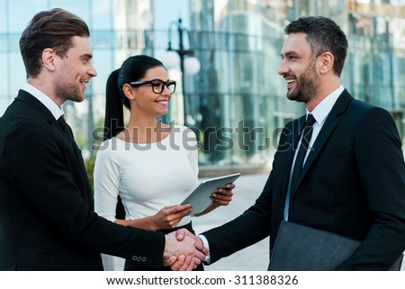 Glad to see you! Two happy young businessmen shaking hands while their female colleague holding digital tablet and smiling