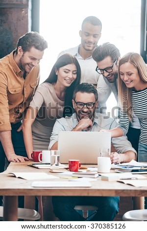 Glad with the results of their work. Group of six cheerful young business people looking at laptop and smiling while looking at laptop together - stock photo