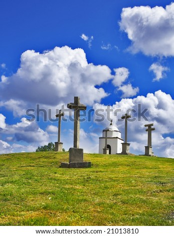 Glade with a chapel and memorable crosses on a background of the spring May sky with clouds