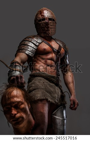 Gladiator covered in blood holding chop off head in his hand