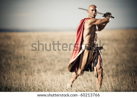Gladiator, image of a well-built man holding a sword and a shield - stock photo