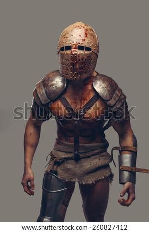 Gladiator in helmet covered in blood  - stock photo