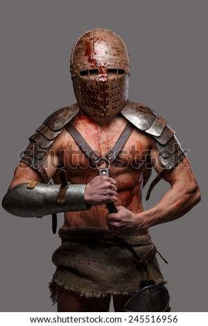 Gladiator in helmet covered in blood standing  - stock photo