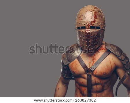 Gladiator in helmet with muscular body covered in blood  - stock photo