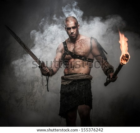 Gladiator standing in a smoke with torch and sword - stock photo