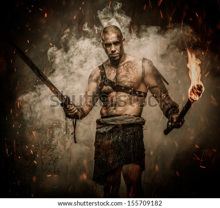 Gladiator standing in a smoke with torch and sword