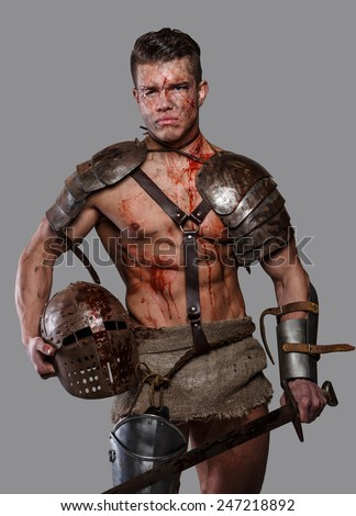 Gladiator with muscular body covered in blood with sword and helmet