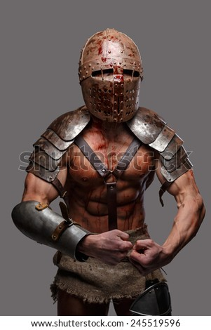 Gladiator with muscular body shows his strength - stock photo
