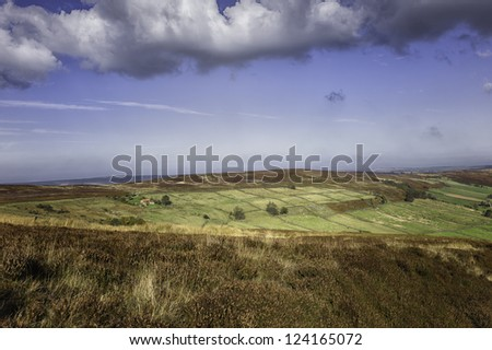 Glaisdale, Yorkshire, UK. View of the North York Moors across the dale of Glaisdale on a bright sunny day in autumn. The heather is still in bloom. Deep in the valley is a farmhouse. - stock photo