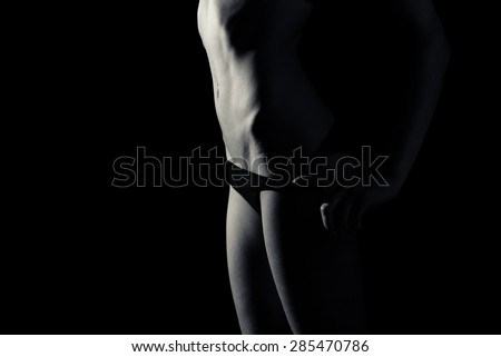 glamor girl having fun posing showing her sexy fitness hips in black lingerie on black copy space background, close up picture - stock photo