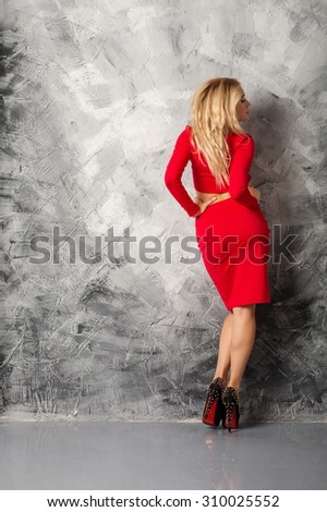 Glamor Sexy  Blonde Girl in red standing back to camera on High Heel - stock photo
