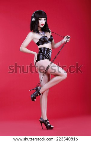 Glamor. Woman DJ in Heels and Stagy Latex Costume with Headphones - stock photo