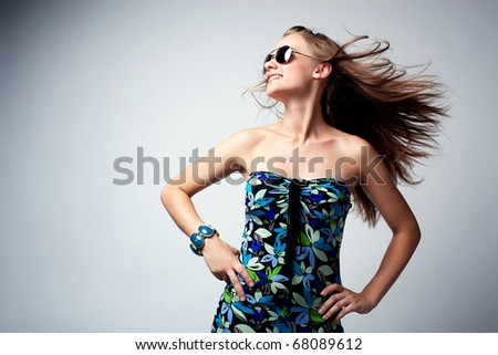Glamor woman posing in studio with sunglasses and colorful dress.