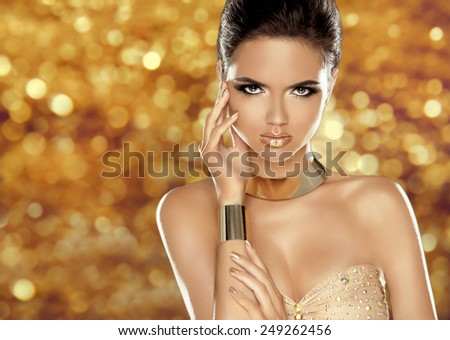 Glamorous beauty fashion girl portrait. Beautiful Young Woman over golden holiday bokeh lights background. Luxury jewelry, makeup, accessories.