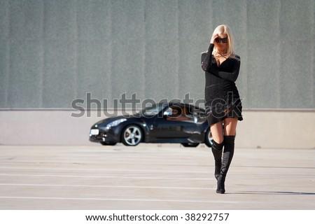 Glamorous blond babe near tuned supercar - stock photo