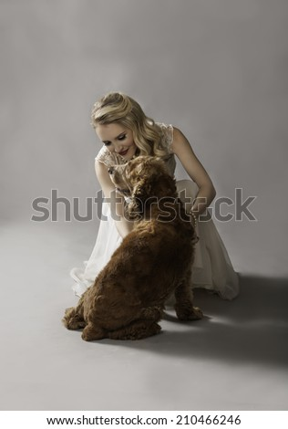 Glamorous blonde woman in vintage dress playing affectionately with her adorable dog - stock photo