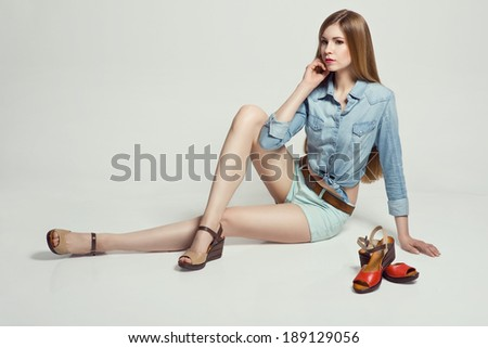 Glamorous blonde woman sitting in the studio presenting summer shoes  - stock photo