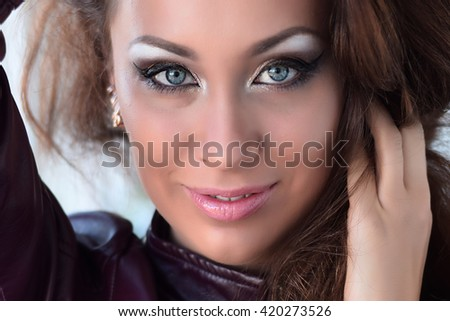 Glamorous brunette in purple leather jacket and sparkly bra with beautiful makeup - stock photo