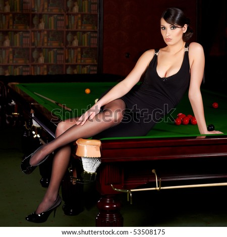 Glamorous brunette sexy woman sitting on a snooker table - stock photo