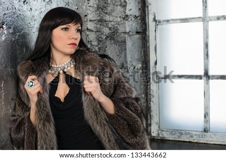 Glamorous dark-haired woman wearing fur coat and jewelry - stock photo