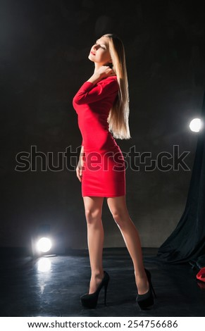 Glamorous  dreamy young woman  wearing red dress standing on stage and touching her neck. - stock photo