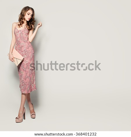 Glamorous Fashion Model Woman Standing on Background - stock photo
