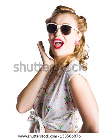 Glamorous female pinup with sunglasses wearing pretty dress with floral decoration  shouting out a warning or recommendation on white background - stock photo