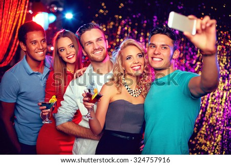 Glamorous friends with cocktails making selfie at party