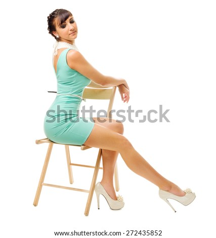 Glamorous girl in turquoise dress and chair isolated - stock photo