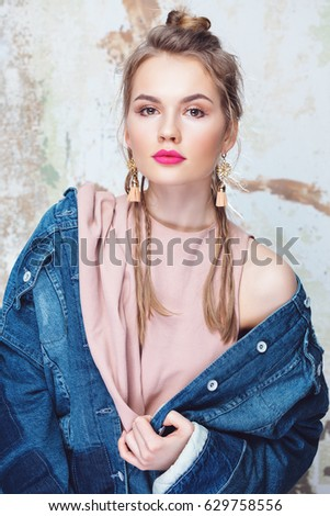 Glamorous girl with bright pink lips wearing rough denim jacket and delicate silk top