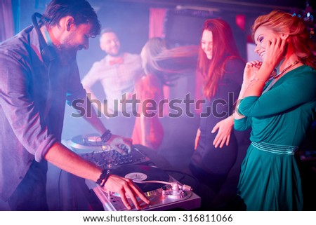 Glamorous girls dancing by dj adjusting sound on turntables in night club - stock photo