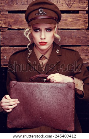 Glamorous intense young female army recruit with blond ringlets clutching an old leather suitcase sitting gazing at the camera against a wooden wall - stock photo