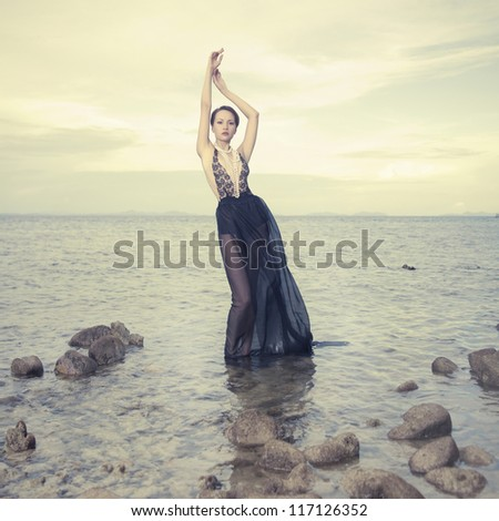 Glamorous lady in an gorgeous dress standing in sea - stock photo