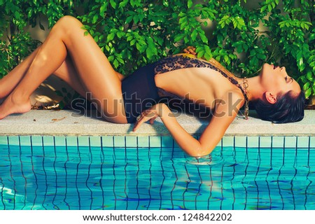 Glamorous lady in lace leotard lies on the side of the pool - stock photo