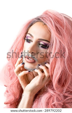 Glamorous man in drag queen make-up with heavy mascara on eyes, glittery beard, wild hair and long nails on white background.