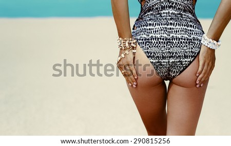 Glamorous Model in fashionable Swimsuit and Stylish Accessories at the beach - stock photo