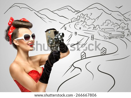 Glamorous pin-up girl filming nature and countryside with an old retro cinema 8 mm camera, standing in front of a road on grey sketchy background. - stock photo
