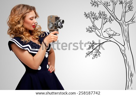 Glamorous pin-up sailor girl filming nature and wildlife with an old retro cinema 8 mm camera, standing in front of a bird on grey sketchy background. - stock photo