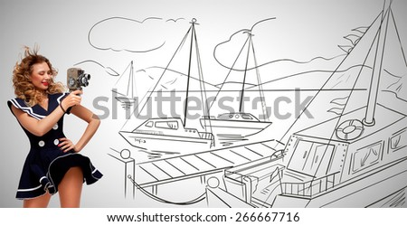 Glamorous pin-up sailor girl in seaport filming yachts with an old retro cinema 8 mm camera and standing in the wind on grey sketchy background. - stock photo